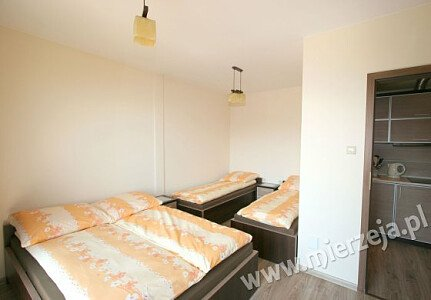 Sypialnia w apartamencie nr 5. Wygodne łoże małżeńskie i łóżka hotelowe.