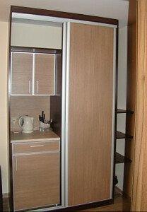 Aneks kuchenny i garderoba. W aneksie znajduje się lodówka, czajnik i naczynia.